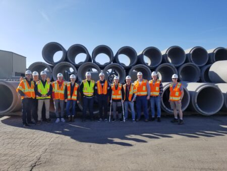 Workers pose in front of concrete pipes