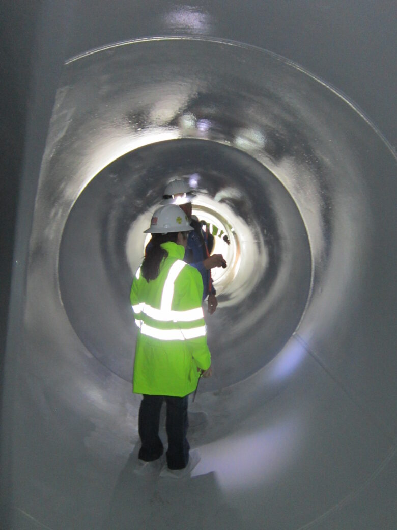 workers inside epoxy lined pipe