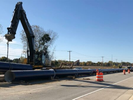 racine water transmission crane with long pipe in road