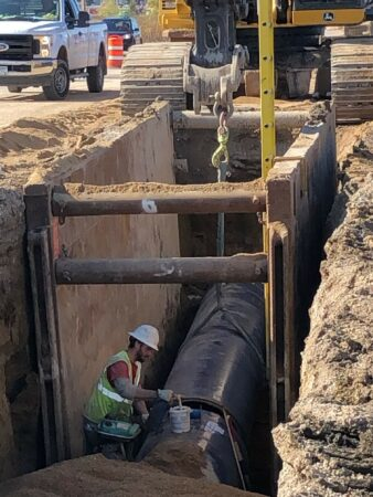 racine water transmission man working on pipe in trench