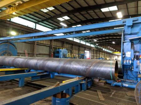 Engineered steel pipe being machine fabricated