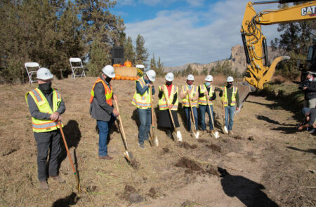 6 people in hard hats and vests with shovels standing in rural area with crane in background