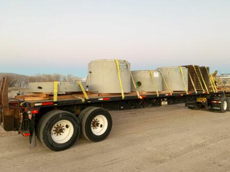 flat bed truck transporting manholes