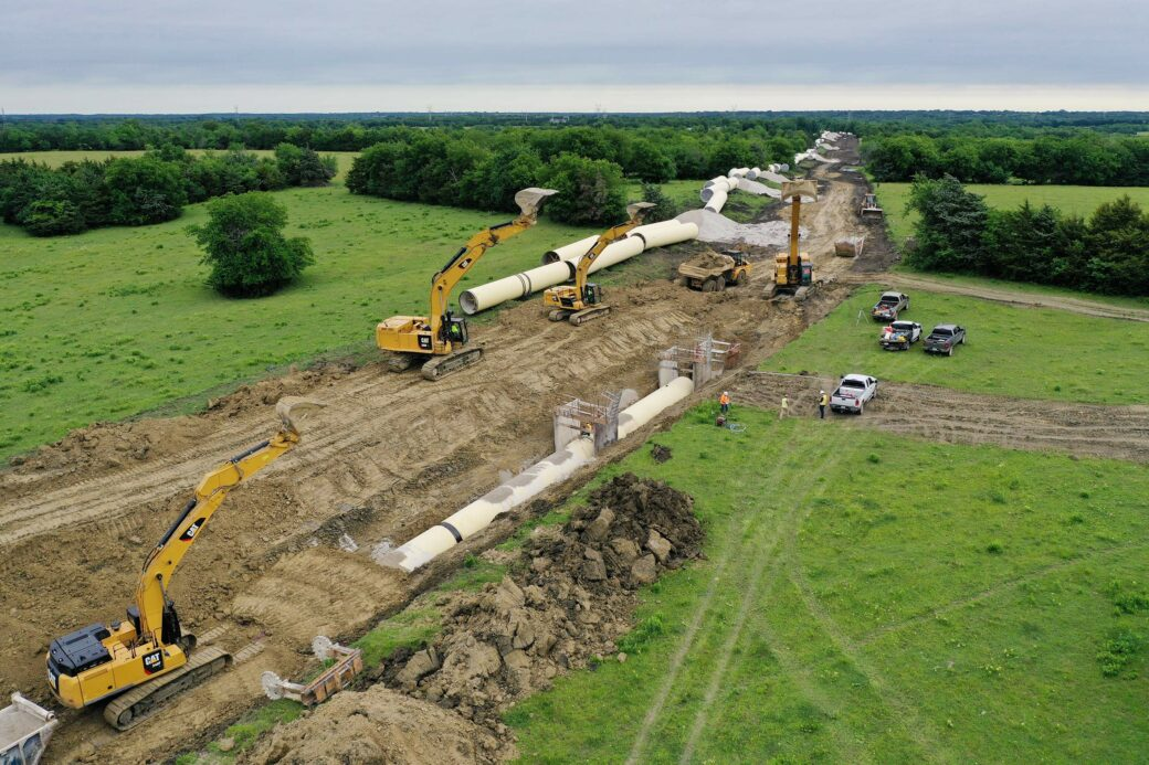 Large diameter steel pipe being installed by cranes into trench dug into grassy landscape