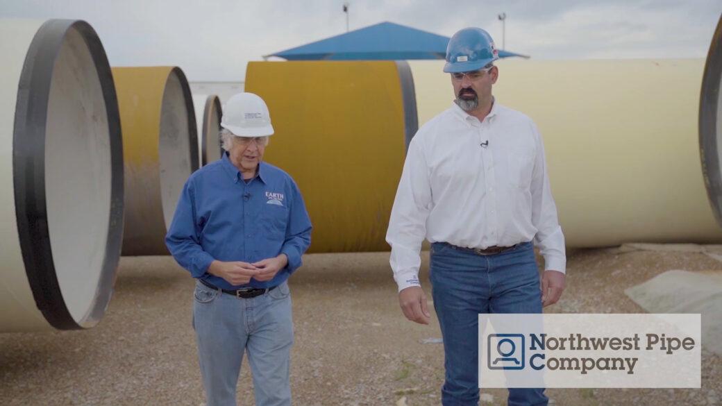 John Holden and Eric Stokes walking amongst large diameter steel pipe