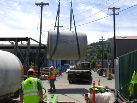 Concrete jacking pipe being lifted by crane for installation