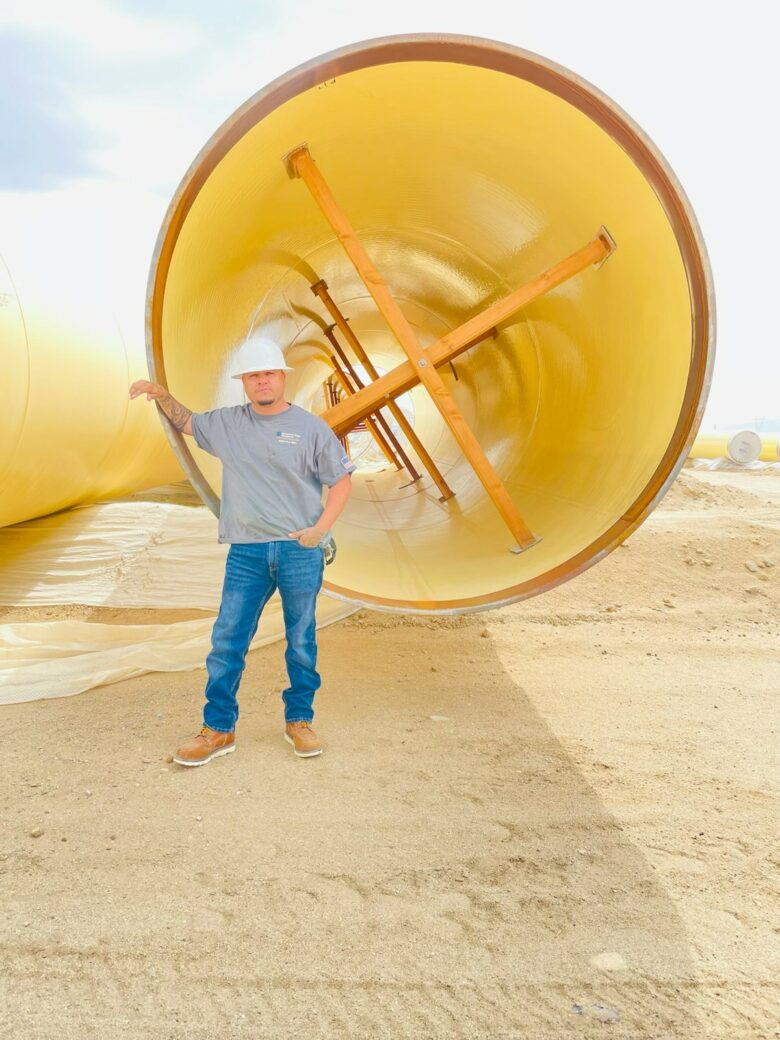 Jose Figueroa in hard hat standing next to Large Diameter Pipe